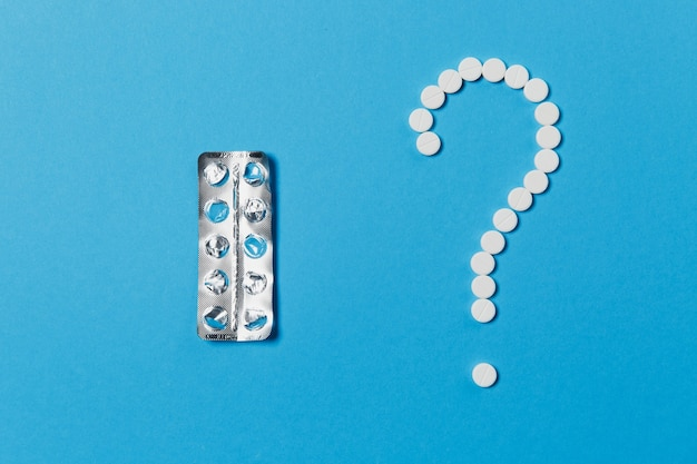 Comprimidos redondos brancos de medicação dispostos em forma de ponto de interrogação isolado em um fundo de cor azul