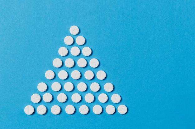Comprimidos redondos brancos de medicação dispostos em um triângulo isolado em um fundo de cor azul