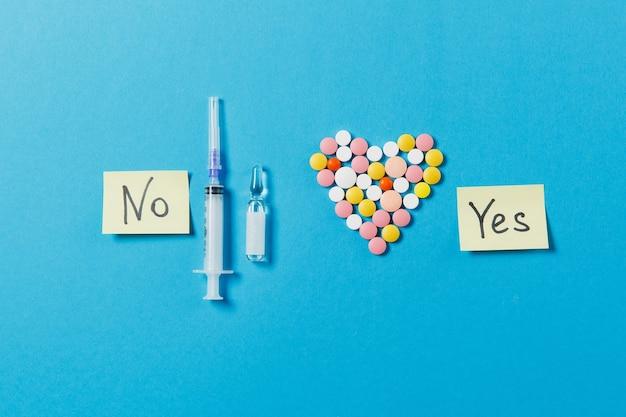 Comprimidos redondos brancos e coloridos de medicação em forma de coração isolada sobre fundo azul