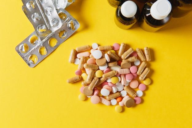 Comprimidos redondos coloridos brancos de medicação dispostos abstratos em um fundo de cor amarela