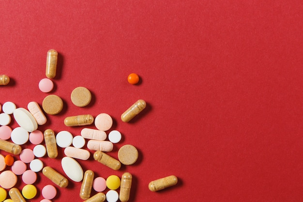 Comprimidos redondos coloridos brancos de medicação dispostos abstratos em um fundo de cor vermelha