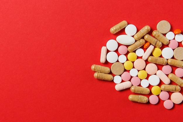 Comprimidos redondos coloridos brancos de medicação dispostos abstratos sobre fundo de cor vermelha. aspirina, pílulas de cápsula para design. saúde, tratamento, conceito de estilo de vida saudável de escolha. copie o anúncio do espaço.