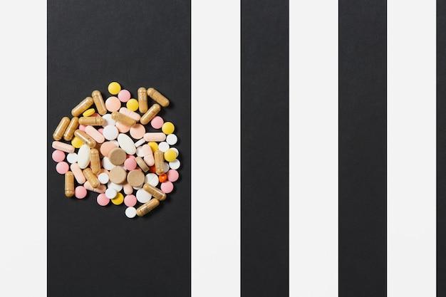 Comprimidos redondos coloridos brancos de medicação dispostos de forma abstrata em fundo preto branco
