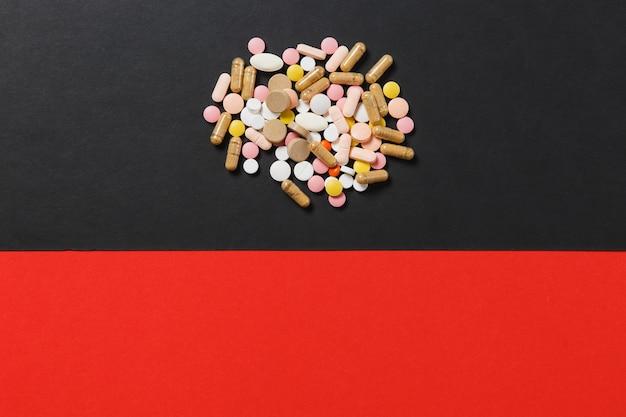 Comprimidos redondos coloridos brancos de medicação dispostos de forma abstrata em fundo preto vermelho