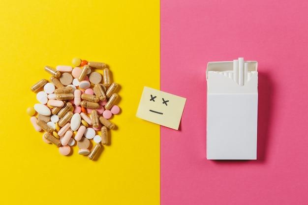 Comprimidos redondos coloridos brancos de medicação dispostos em pacotes abstratos de cigarros brancos em um fundo de cor amarela