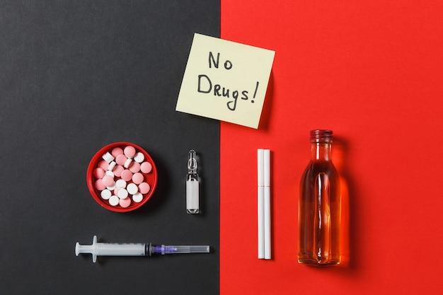Comprimidos redondos coloridos comprimidos de medicação, agulha da seringa vazia, cigarros de ampola de garrafa de álcool em fundo vermelho preto. o texto da folha de adesivos de papel não atrai drogas. estilo de vida saudável de escolha de tratamento.