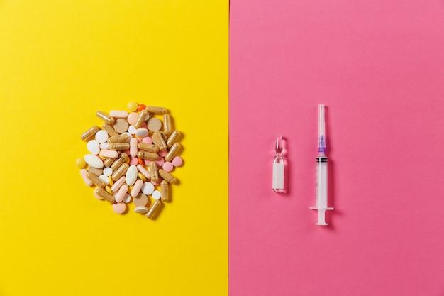 Comprimidos redondos coloridos de medicação, cápsulas, comprimidos dispostos de forma abstrata sobre fundo rosa amarelo. aspirina, ampola, agulha da seringa vazia. saúde, tratamento, escolha, conceito de estilo de vida saudável. copie o espaço.