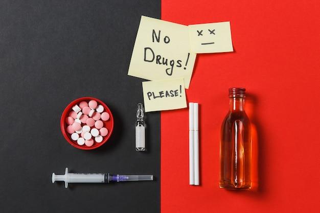 Comprimidos redondos coloridos de medicação, pílulas, agulha de seringa vazia, garrafa de cigarros com ampola de álcool