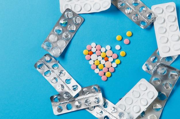 Comprimidos redondos coloridos de medicamentos em forma de coração de difusão isolado sobre fundo azul