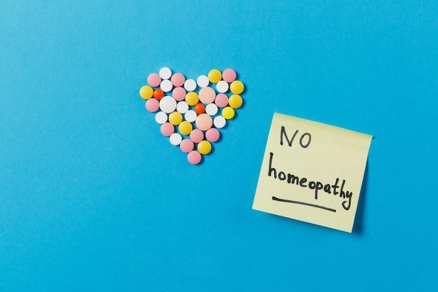 Comprimidos redondos coloridos de medicamentos em forma de coração isolada sobre fundo azul