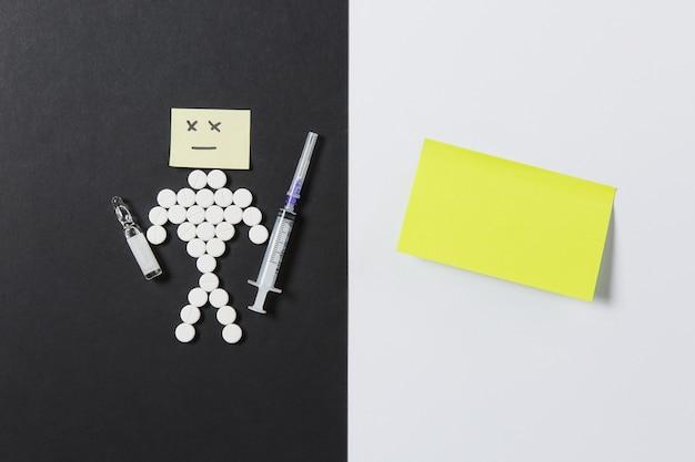 Comprimidos redondos de medicação dispostos humanos tristes em fundo branco e preto. etiqueta amarela, agulha da seringa vazia da ampola, design de pílulas. conceito de estilo de vida saudável de escolha de tratamento. copie o anúncio do espaço.