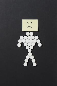 Comprimidos redondos de medicamentos brancos dispostos como um homem em fundo preto