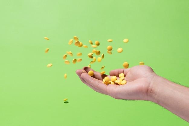 Comprimidos remédios amarelos voando na mão