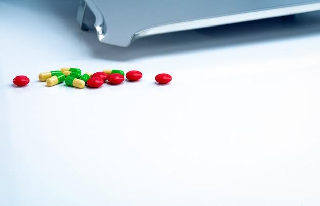 Comprimidos revestidos de açúcar redondos vermelhos e cápsulas verde-amarelas com bandeja de medicamentos em aço inoxidável na mesa branca. farmacêutica conceito. indústria farmacêutica. produtos de farmácia. cuidados de saúde e medicamentos.