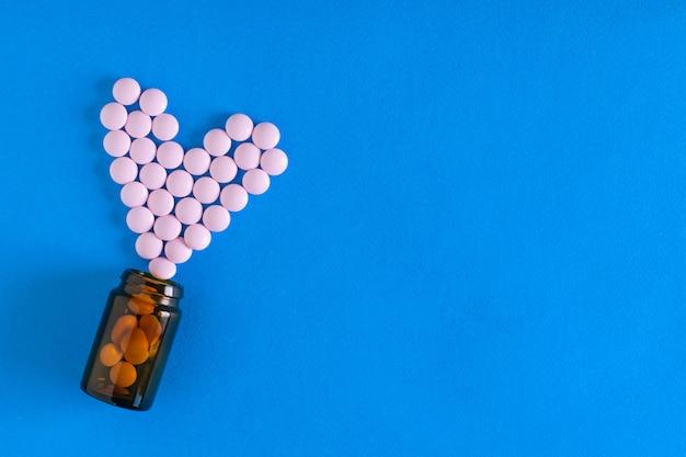 Comprimidos rosa são derramados de uma bolha de vidro marrom na forma de um coração