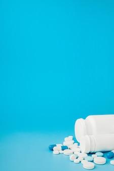 Comprimidos sortidos de medicina farmacêutica, comprimidos e cápsulas e garrafa sobre fundo azul. copie o espaço para texto