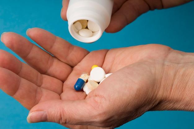 Comprimidos, tabuletas e drogas que derramam da garrafa médica branca na mulher. fechar-se