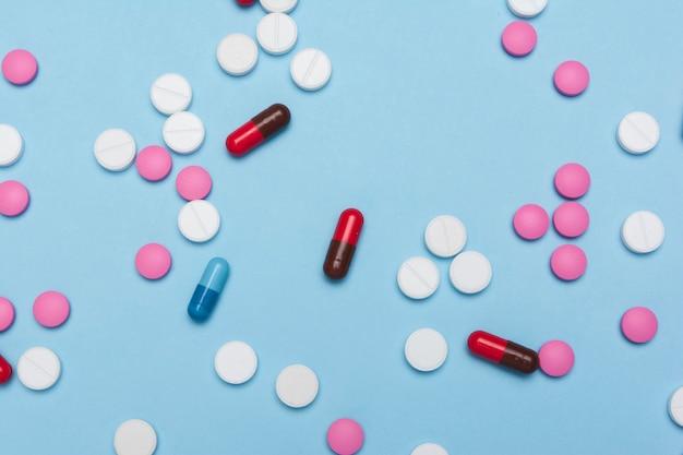 Comprimidos / tema da farmácia / comprimidos e cápsulas coloridos na superfície azul. configuração plana