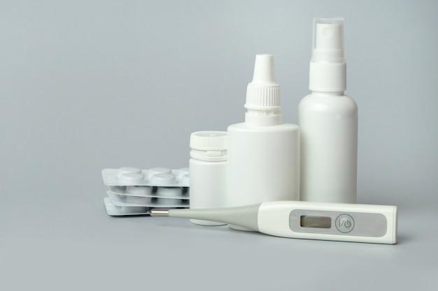Comprimidos, termômetro, desinfetante para as mãos e spray de nariz em fundo cinza. conjunto de tratamento para gripes e resfriados. conceito de tratamento de doenças.