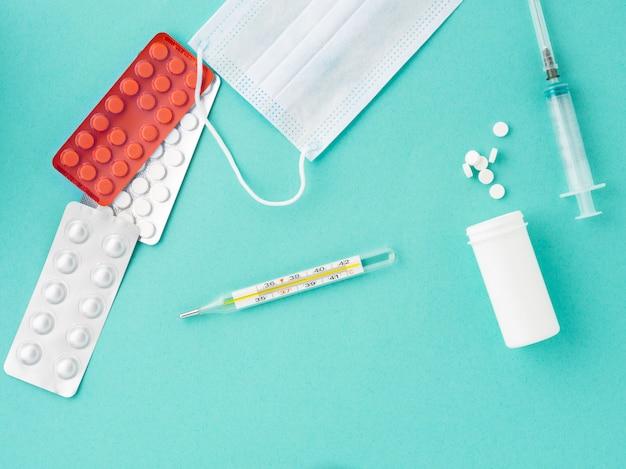 Comprimidos, termômetro, máscara protetora médica, seringa em um fundo azul, vista superior.