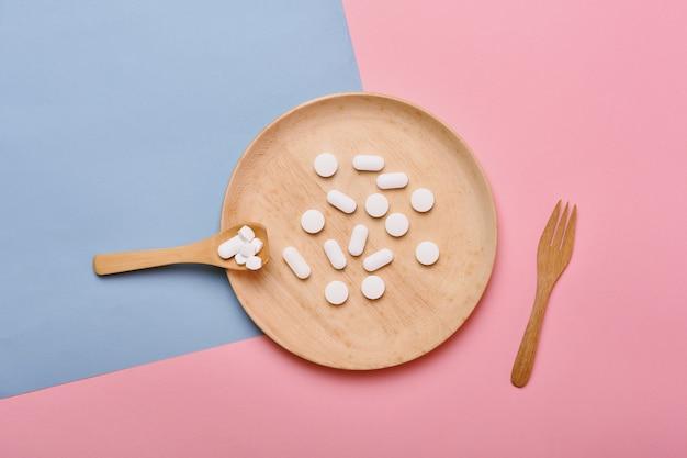 Comprimidos variados em um prato de madeira e colher