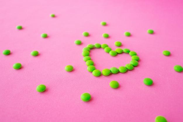 Comprimidos verdes e comprimidos em forma de coração, comprimidos revestidos de coração para cardiologia de doenças cardíacas, prebióticos e suplementos probióticos para saúde intestinal, conceito de farmácia e hospital