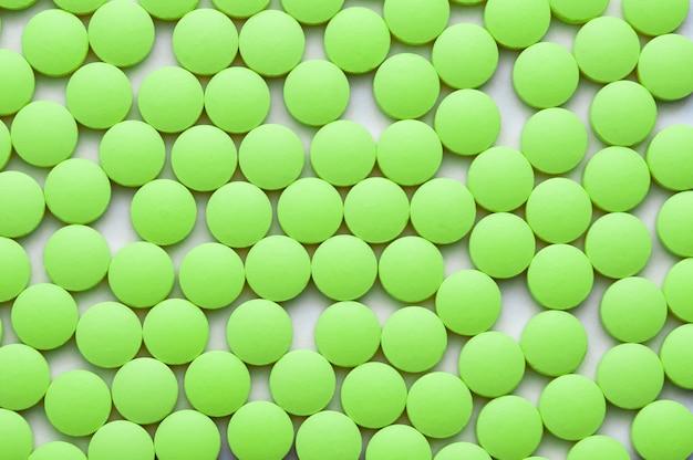 Comprimidos verdes pequenos em um close-up branco do fundo.