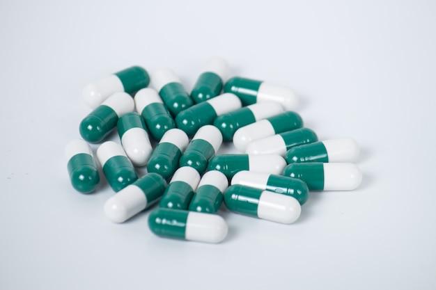 Comprimidos verdes um frasco de comprimidos no fundo branco
