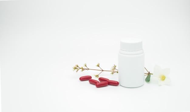 Comprimidos vermelhos da cápsula da vitamina e do suplemento com flor e ramo com a garrafa plástica da etiqueta em branco no fundo branco com espaço da cópia, apenas adicione seu próprio texto
