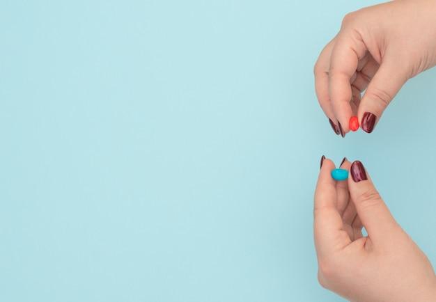 Comprimidos vermelhos e azuis em mãos femininas