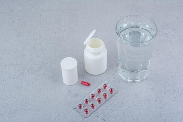 Comprimidos vermelhos, recipientes e copo d'água na superfície de mármore