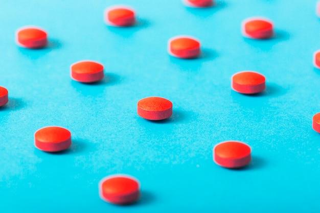Comprimidos vermelhos redondos sobre o pano de fundo azul