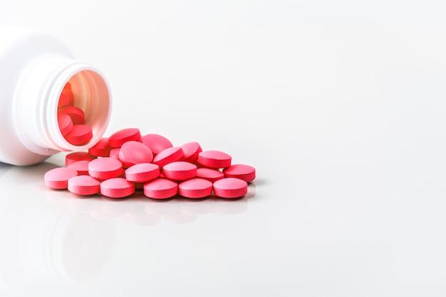 Comprimidos vermelhos são espalhados de um frasco