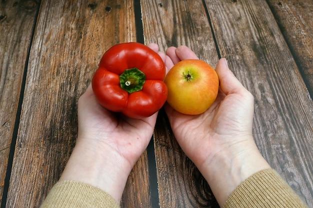 Comprimidos versus alimentos saudáveis, uma mão toma comprimidos perto de maçã fresca e pimentão