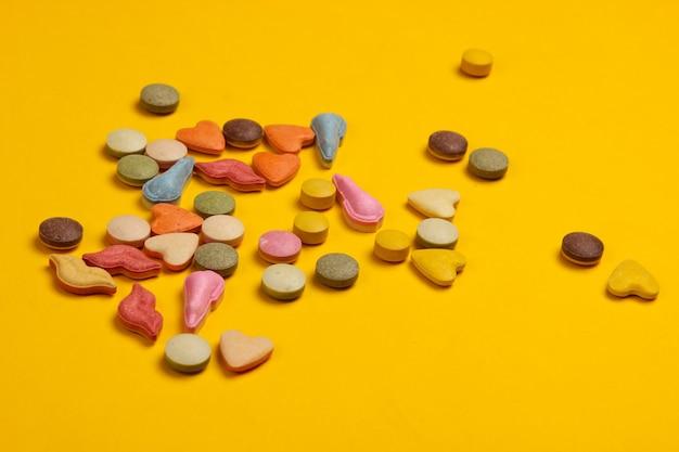Comprimidos veterinários de vitaminas com formas diferentes para gatos em um amarelo