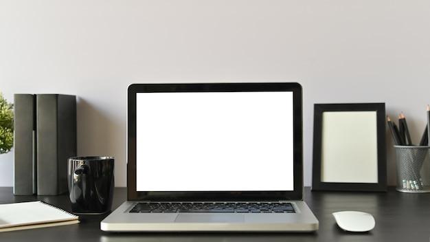Computador, café e material de escritório do espaço de trabalho do escritório no foco seletivo da tabela preta.