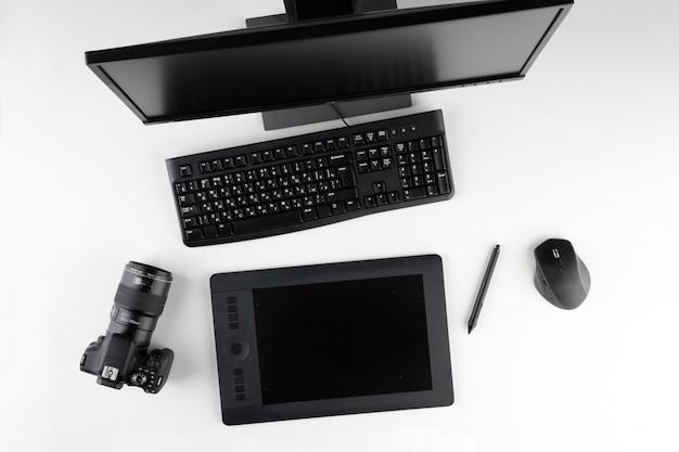 Computador, câmera e tablet na mesa. computador de mesa com ferramentas de retoque de fotos. espaço de trabalho criativo moderno do fotógrafo ou designer