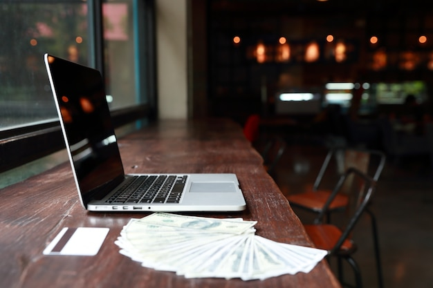 Computador com dinheiro e cartão de crédito na mesa