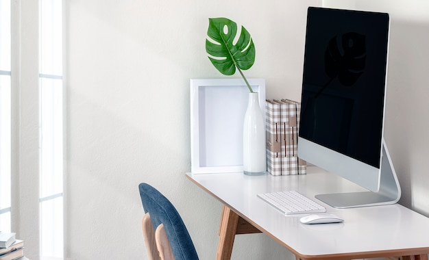 Computador com tela em branco e planta de casa