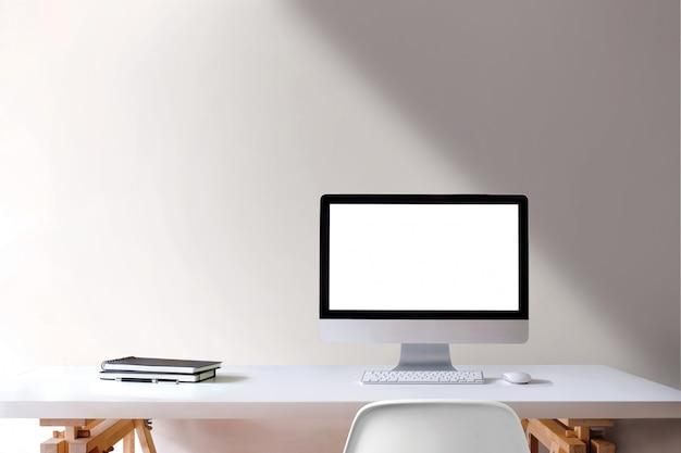 Computador da tela vazia do desktop do espaço de trabalho na tabela de madeira branca.