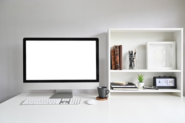 Computador de área de trabalho na mesa de escritório e livros, moldura e livros nas prateleiras.