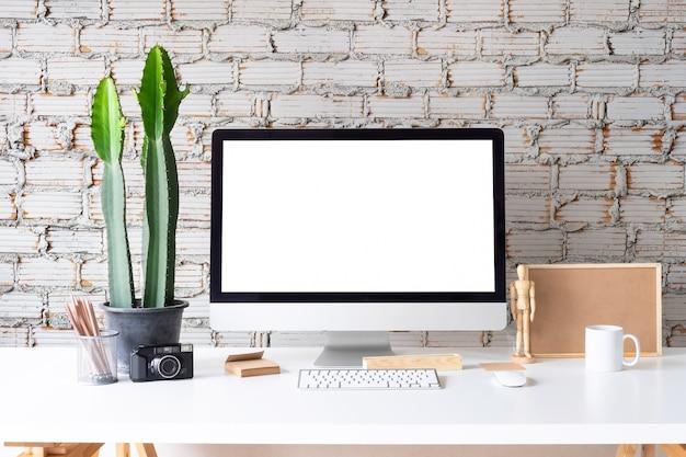 Computador de maquete do espaço de trabalho com caneca de café, jarra de lápis e o bloco de notas na mesa branca