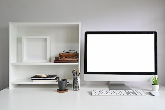 Computador de maquete do espaço de trabalho na mesa de escritório e livros, moldura e livros nas prateleiras.