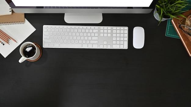 Computador de mesa de escritório e material de escritório com café na mesa preta.