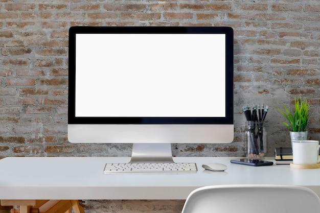 Computador de secretária da tela vazia na mesa branca sobre a parede no escritório do estúdio.