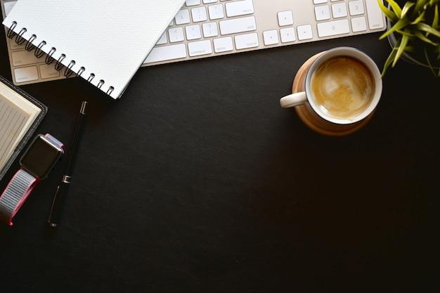 Computador de teclado de mesa de escritório de couro escuro moderno, óculos, caneca de café, planta de casa e espaço de cópia