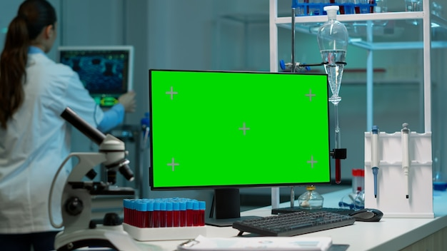 Computador desktop com tela verde, simulação em exibição colocada na mesa em um laboratório científico enquanto uma cientista pesquisadora médica analisando a evolução do vírus em um monitor digital conduzindo um experimento