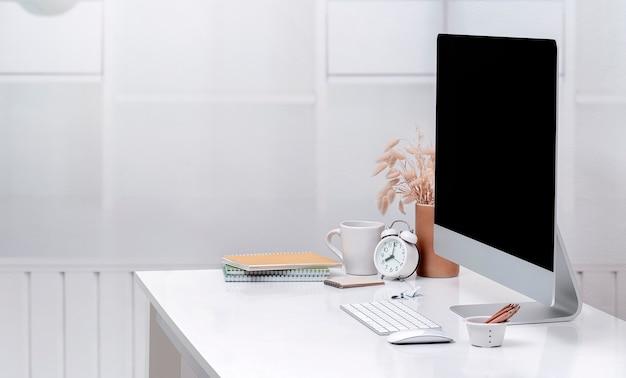 Computador desktop de maquete e suprimentos na mesa superior branca. tela em branco para design gráfico. copie o espaço.