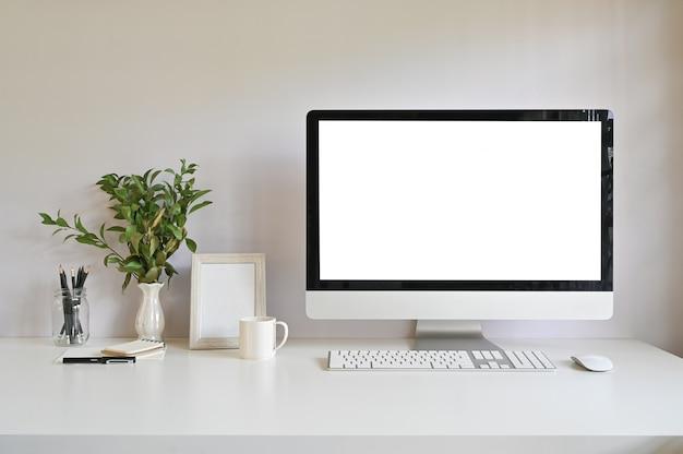 Computador do espaço de trabalho e frame da foto, café com a decoração da planta na mesa de escritório.