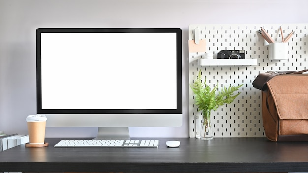 Computador e café na mesa com pegboard